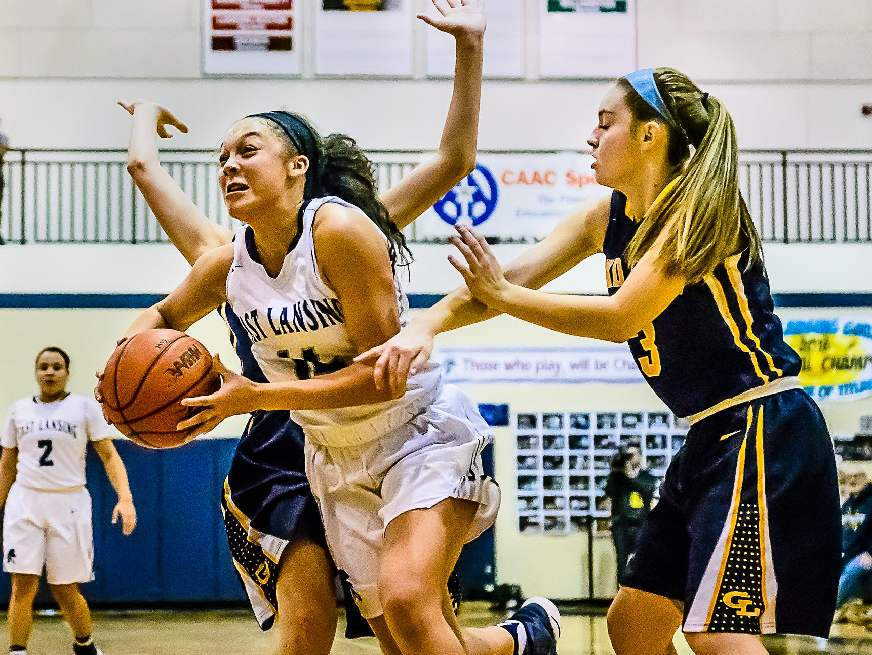 Aazhenii Nye ,center, of East Lansing splits Grand Ledge defenders Allyson Hunt ,left, and Mackenzie Todd ,right, on herway to the Grand Ledge basket during their district semifinal game Wednesday March 1, 2017 at East Lansing High School. KEVIN W. FOWLER PHOTO