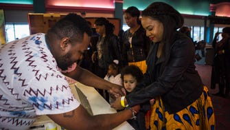"""February 17, 2018 - Timothy Green, Jr., left, gives a wristband to Lisa Berry as she and her son, Caiden Berry, 5, arrive to Malco Stage Cinema to watch a screening of Black Panther in Bartlett on Saturday. Green served as co-host for the special event. """"We went from having a goal of $1800 to being able to raise over $2400 for this event,"""" Green said, who expected to have between 150 to 170 people arriving to see the superhero film. Green also serves as executive director and founder of The Dividend - an organization that """"invests in young men of color in order to yield positive results for our community,"""" according to Green. """"And this is just one way that we're doing that."""""""