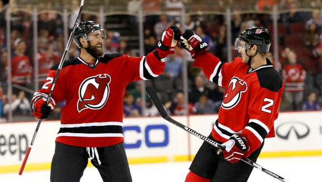 The Devils' Kyle Quincey, left, and John Moore.