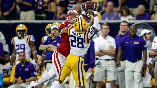LSU Tigers safety Jalen Mills (28) intercepts a pass intended for Wisconsin Badgers tight end Troy Fumagalli (48) during the fourth quarter at NRG Stadium. The Tigers defeated the Badgers 28-24.