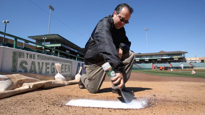 Press staff writer Jerry Carino spray-paints the bullpen pitching rubber at FirstEnergy Park before a Lakewood BlueClaws game.