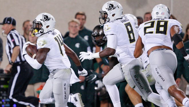 Sep 12, 2015; East Lansing, MI, USA; Oregon Ducks cornerback Ugo Amadi (14) runs after an interception during the second quarter against the Michigan State Spartans at Spartan Stadium. Mandatory Credit: Raj Mehta-USA TODAY Sports