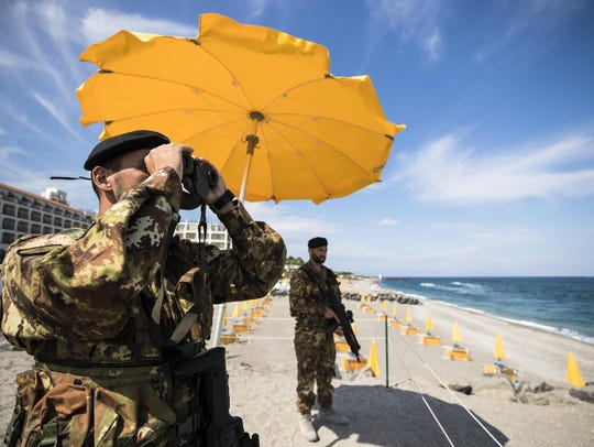 Italian soldiers stand on the beach in Giardini Naxos