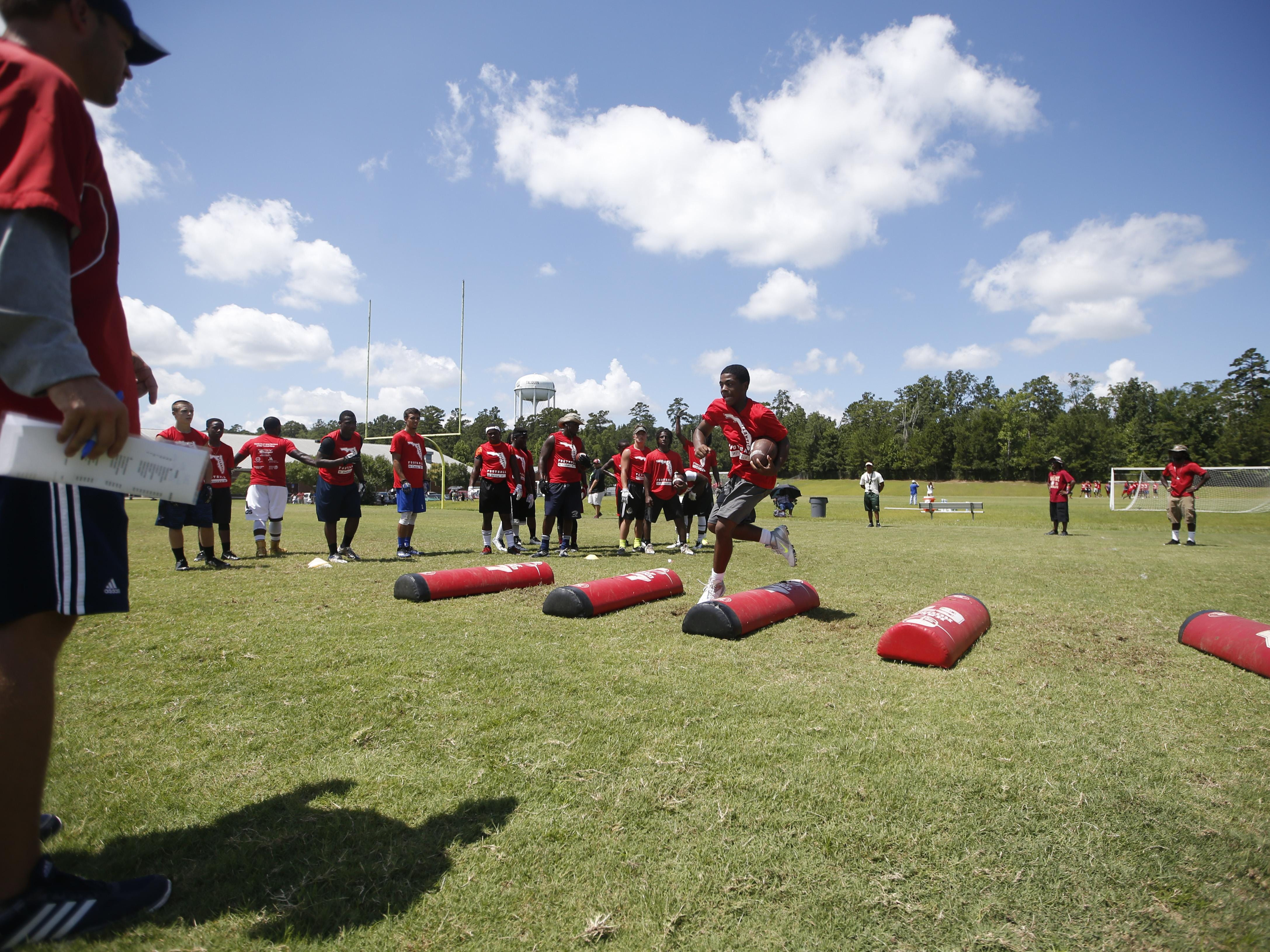 High school players run through drills during the Florida Atlantic Football Camp at Lawson Chiles High School on Friday.