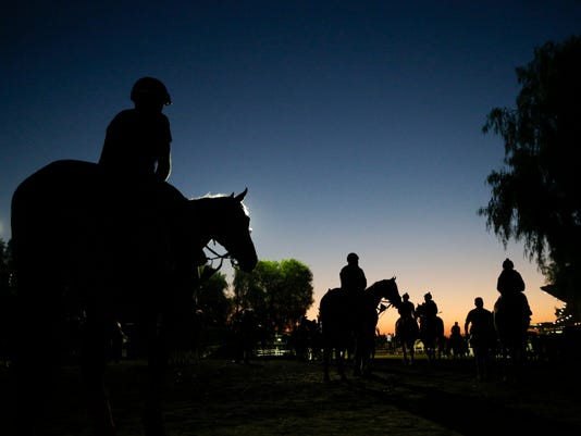 Riders and horses walk toward the track for a morning workout ahead of the Breeders' Cup races at Santa Anita Park Wednesday, Oct. 29, 2014, in Arcadia, Calif. (AP Photo/Jae C. Hong)