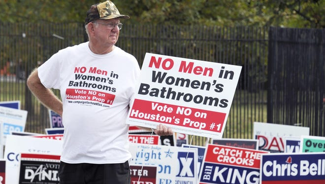 A demonstrator holds a sign against the Houston Equal Rights Ordinance outside an early voting center in Houston. The anti-bias ordinance was repealed in a November 2015 referendum.