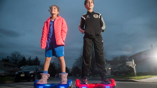 Eleven-year-old twins Trey (right) and Kasey Shaw ride their hoverboards in front of their Cherry Hill home.