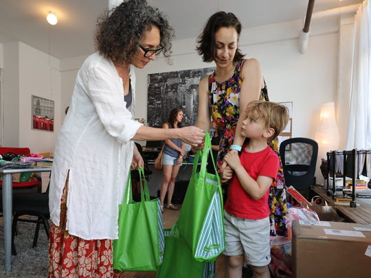 Pam Koner, left, the executive director of Family-to-Family in Hastings-on-Hudson, takes in a bag of donated items from Libby Copeland and her son, Lev Berko, 4, June 29, 2018. The center has been collecting items for unaccompanied immigrant children being held at Children's Village in Dobbs Ferry.