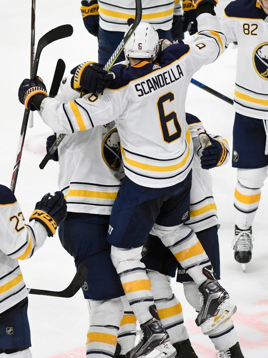 Buffalo Sabres defenseman Marco Scandella (6) leaps into the arms of center Ryan O'Reilly and center Scott Wilson after scoring in overtime against the Detroit Red Wings in an NHL hockey game, Thursday, Feb. 22, 2018, in Detroit. The Sabres won 3-2. (AP Photo/Jose Juarez)