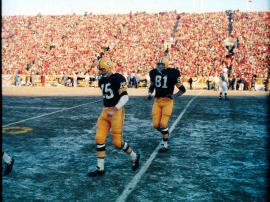 Green Bay Packers quarterback Bart Starr (15) and tight end Marv Fleming go to the sideline during the NFL championship game on Dec. 31, 1967. Joe Bowers of Appleton took this Ice Bowl photo after sneaking onto the Packers's sideline.