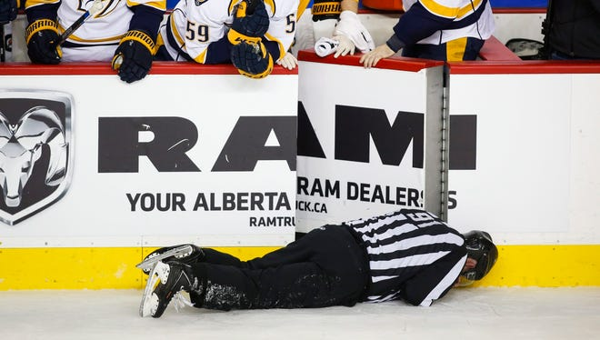 Nashville Predators' players look over the bench at linesman Don Henderson after he was hit by Calgary Flames' Dennis Wideman during the second period Wednesday night.