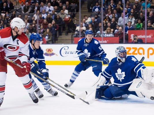 Toronto Maple Leafs goalie Jonathan Bernier (45) makes a pad save against Carolina Hurricanes center Eric Staal (12) during the first period of an NHL hockey game Thursday, Feb. 25, 2016, in Toronto. (Nathan Denette/The Canadian Press via AP)