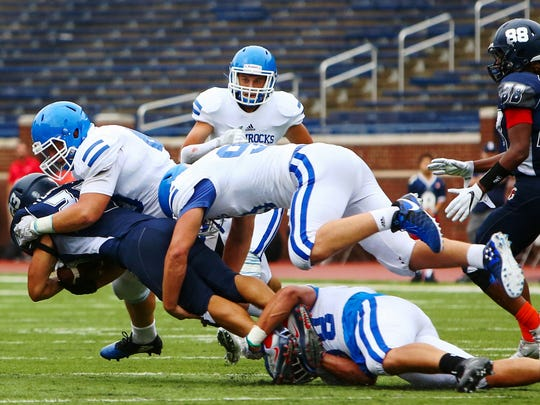Catholic Central's defense of Tyler St. Clair (top), Jackson Ross (middle) and Isaac Darkangelo (low) gang tackle a Stevenson runner.