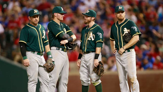 Athletics shortstop Nick Punto (1), third baseman Josh Donaldson (20),  second baseman Eric Sogard (28) and first baseman Brandon Moss (37) talk during a pitching change.