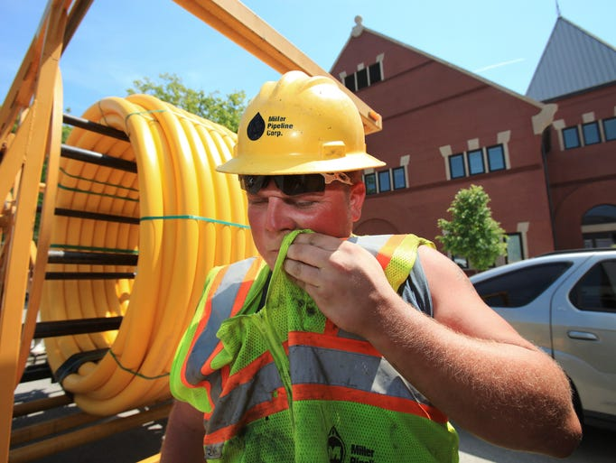 Drew Strahan wiped sweat from his face after using a jack hammer to prepare for the installation of a gas line on Jackson Street near Jefferson Street.  Today may be the warmest day of the year. May 7, 2014