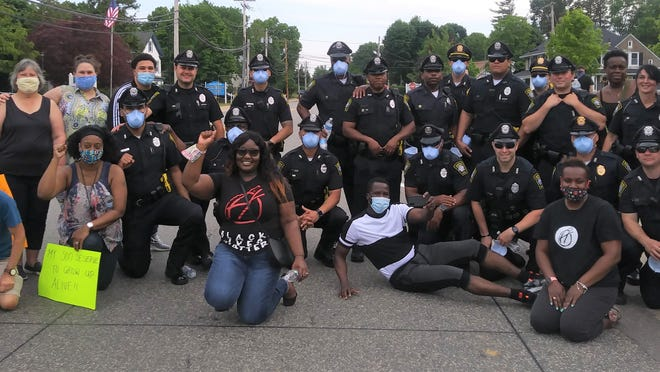Organizer Allaphia Sackeena Richards-Jean Pierre (centeer, with hand raised), police and others assemble at the Randolph rally for racial equality on Thursday afternoon, June 4.
