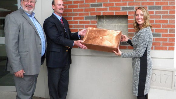 Stevens Point Mayer Michael Wiza, Jeff Martin, Regional Vice President, Ministry Health Care and Crystal Kirschling, Chief Administrative Officer and Vice President of Patient Care Services at Ministry Saint Michael's Hospital, place a time capsule as part of the celebration event.