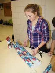 Madison Serovy, a sixth grader at Clear Creek Amana Middle School, measures gift wrapping for a package during Wrappin for a Cause Thursday, Dec. 17, at the middle school in Tiffin.