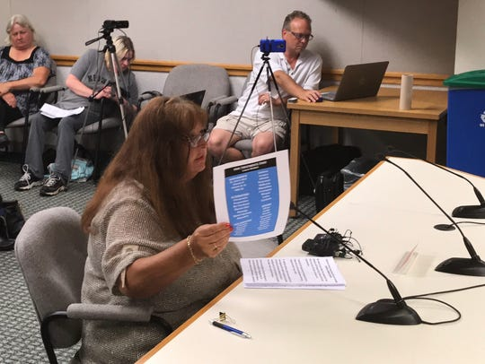 While addressing Brown County supervisors Monday night, Howard resident Laura Kiefert holds a list of pain treatments she has been prescribed for glaucoma and painful diabetic conditions. She says legal marijuana could provide relief without dangerous side effects associated with opioids and other prescription painkillers.