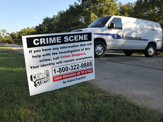 A sign outside the October 2016 crime scene at Lucy Park informs the public to call Crime Stoppers with information in the murder of Roger Aliff.