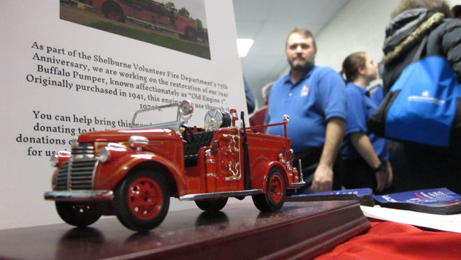 Shelburne Firefighter Dana Baker stands behind a model 1941 Buffalo fire engine at the pre-Town Meeting Day gathering Monday night in Shelburne. Baker and others are leading volunteer efforts to renovate the actual truck in time for the Fire Department's 75th birthday this summer.