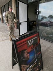 Sgt. Graham Kimmel stands at the door of the newly opened Howell Army Recruiting Station on Latson Road in Genoa Township Wednesday, April 11, 2018.
