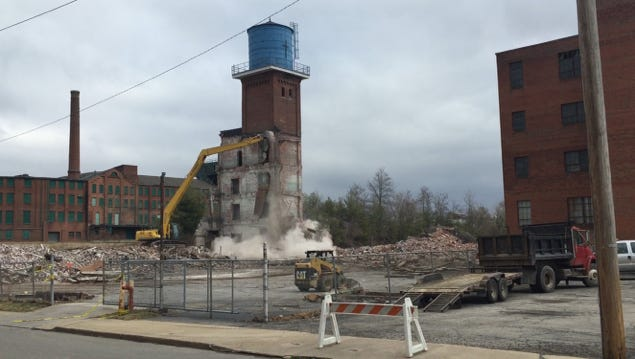 The water tower was scheduled to come down Thursday but a hydraulic line burst on a bulldozer delaying the demolition until Friday.