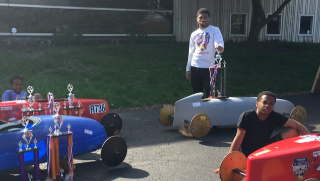 Geordan Wells, center, shows off Soap Box Derby awards and hand-built cars with brothers Matthew and Marcus. Geordan was nominated for the Soap Box Derby's Youth Service Award, which is given out yearly to kids under 21 for volunteerism and having a positive impact on their local community.