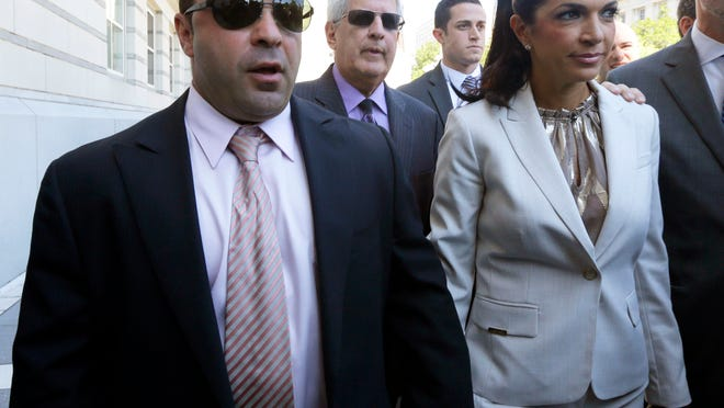 In this July 30, 2013 file photo, 'The Real Housewives of New Jersey' stars Joe and Teresa Giudice, of Montville walk out of Martin Luther King Jr. Courthouse after an appearance in Newark. The couple, who has since pleaded guilty to conspiracy to commit fraud, is now selling their $4 million Montville home.