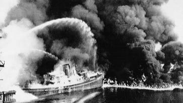 A fire tug fights flames on the Cuyahoga River near downtown Cleveland, Ohio, where oil and other industrial wastes caught fire June 25, 1969.