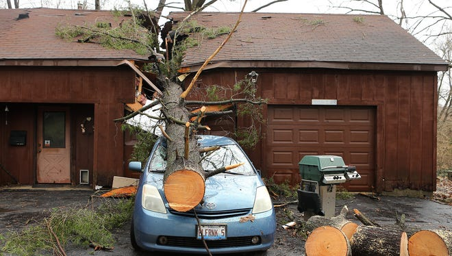 A strong storm sent a tree through a home and garage, landing on a car on Thursday, April 3, 2014, in Belleville, Ill.