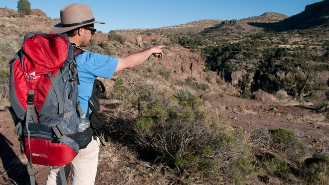 Filmmaker Cameron Trejo looks for a shot as he leaves Rattlesnake Canyon in southern Arizona.
