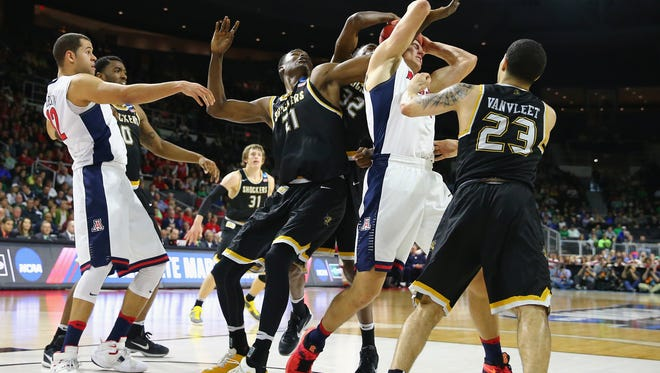 Kaleb Tarczewski of the Arizona Wildcats and Bush Wamukota of Wichita State battle for a rebound during the first round of the 2016 NCAA  Tournament on March 17, 2016 in Providence, Rhode Island.