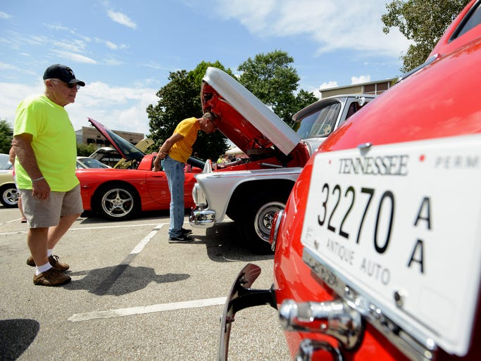 People look at classic cars at the Labor Day Cool Car Cruise-In and Show in Lexington's Court Square Monday. Antique cars, rat rods and trucks were on display for free.