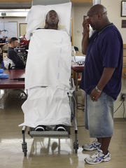 Fletcher Cleaves is attached to a table and held upright for several minutes to benefit his circulation at the Shepherd Center in Atlanta in October 2009. His father, also named Fletcher Cleaves, is at right.