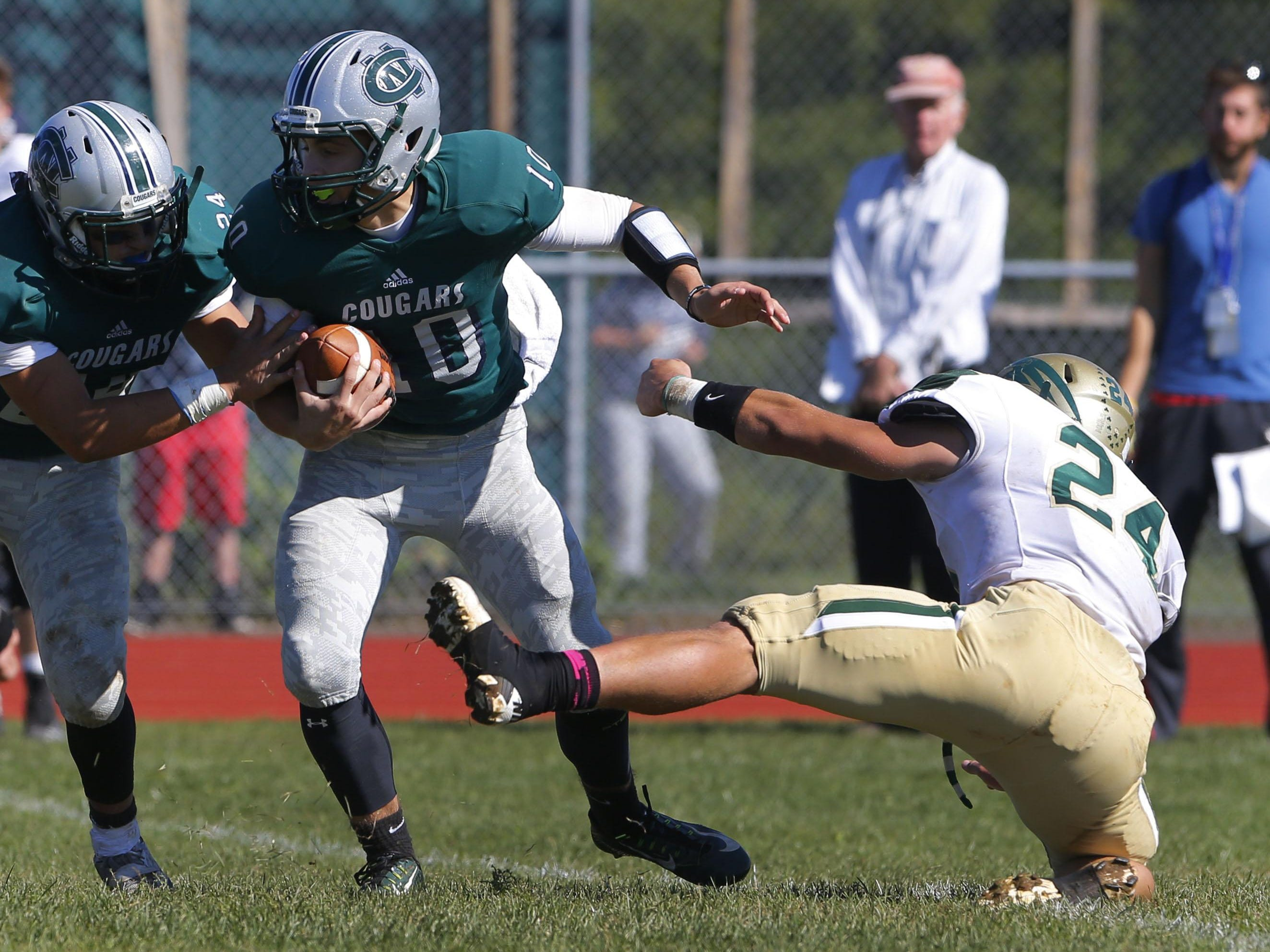 Colts Neck quarter back Hayden Volk (10) of Colts neck avoids the tackle of Dylan Murphy (24) of Red Bank Catholic at Colts Neck High School, Colts Neck,NJ. Saturday, October 10, 2015.