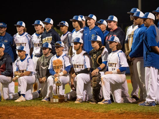 Martin County players and coaches pose with the Robbie Souza Memorial Classic trophy after defeating South Fork 3-1 in the 34th annual game Friday at Tiger Field in Stuart. The Souza game honors the former Martin County and University of Miami standout, who grew up in Indiantown and died in a 1985 car crash at age 21.