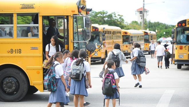 In this file photo, school buses drop off private school students. As school starts, be vigilant for students on their way to classes and stop for buses with flashing lights.