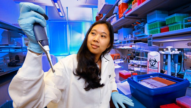 The Helios scholars spent the summer at Translational Genomics Research Institute, working on high-level research. Pictured is Bessie Meechoovet, a research associate at TGen.