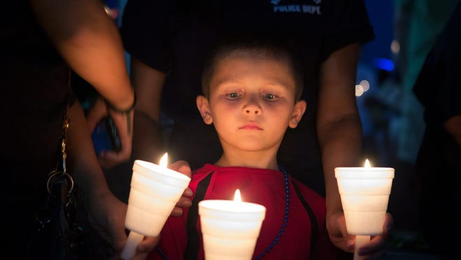 A young boy looks down at his lit candle during a candlelight vigil to honor Officer Daryl Pierson on Thursday.