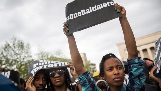Activists protest in front of city hall after marching from the Sandtown neighborhood to demand better police accountability and racial equality following the death of Freddie Gray.