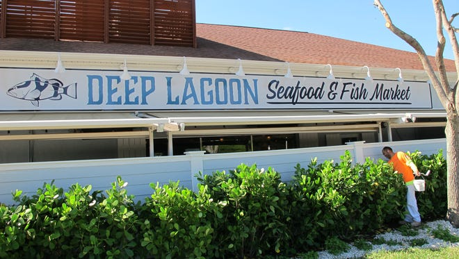 A worker puts finishing touches on Deep Lagoon Seafood & Fish Market, which recently replaced Randy's Fishmarket Restaurant at 10395 U.S. 41 N. in North Naples.