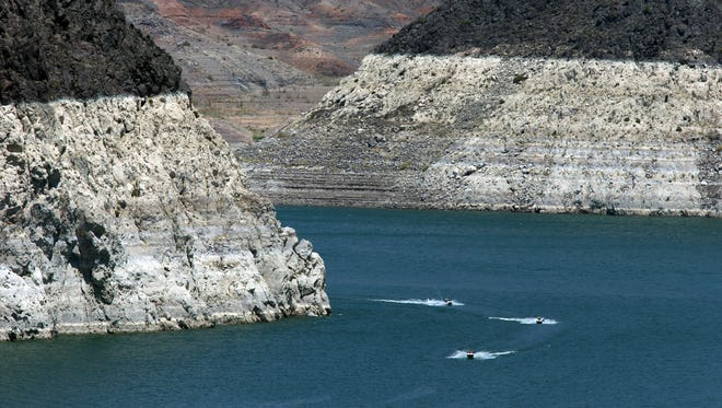Jet skiers cruise June 2015 on Lake Mead. A high-water mark is visible on the shoreline, indicating a 150-foot drop in the lake's water level.
