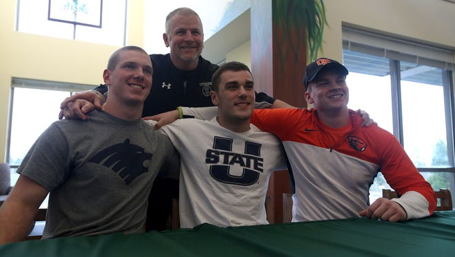 West Salem High School football coach Shawn Stanley, center, poses with seniors Roman Kleiber, left, Cade Smith and Hamilton Hunt on Wednesday, Feb. 4 , 2015, in Salem, Ore.