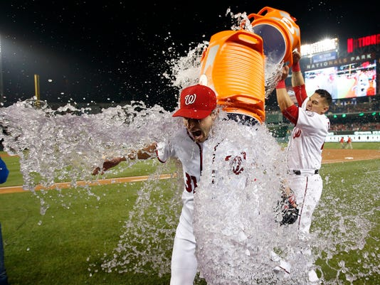 Washington Nationals starting pitcher Max Scherzer is doused by catcher Wilson Ramos after the Nationals defeated the Detroit Tigers in a baseball game at Nationals Park, Wednesday, May 11, 2016, in Washington. Scherzer struck out 20 batters, tying the major league nine-inning record. (AP Photo/Alex Brandon)