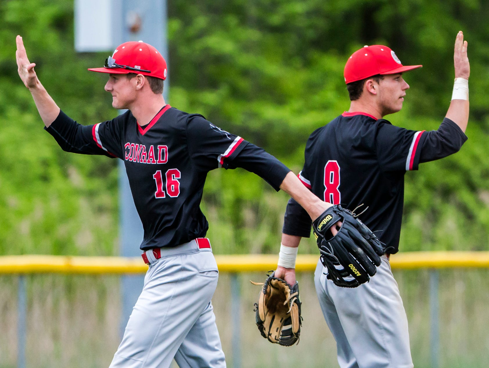 Conrad's Christopher Kramedas (left) and Brett Nowell (right) walk past each other as they high-five teammates following Conrad's 1-0 win over Delaware Military Academy in Newark on Tuesday afternoon.