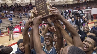 Warren Central High School players celebrate with their trophy after winning the championship game in the 2018 Marion County Boys' Basketball Tournament at Southport High School, Monday, January 15, 2018. Warren Central won 55-43.