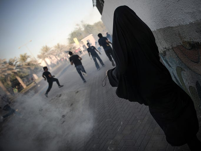 A Bahraini woman stays away from tear gas and bird shot fired by riot police during clashes following the funeral of Ali Khalil Sabbagh in the village of Bani Jamrah, west of Manama, on October 23, 2013. Sabbagh, 17, died when a bomb that he was making blew up, Bahraini police said. AFP PHOTO/MOHAMMED AL-SHAIKH        (Photo credit should read MOHAMMED AL-SHAIKH/AFP/Getty Images)