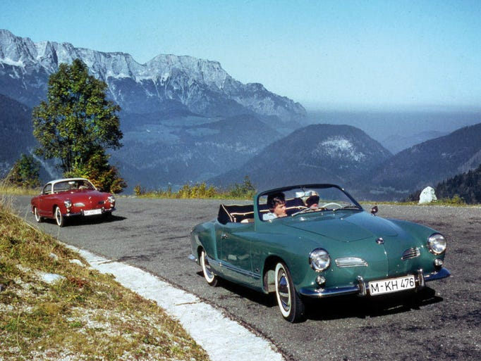 Taking a drive in a Karmann Ghia in the good ol' days. The first coupes were in 1955; convertibles began in 1957.