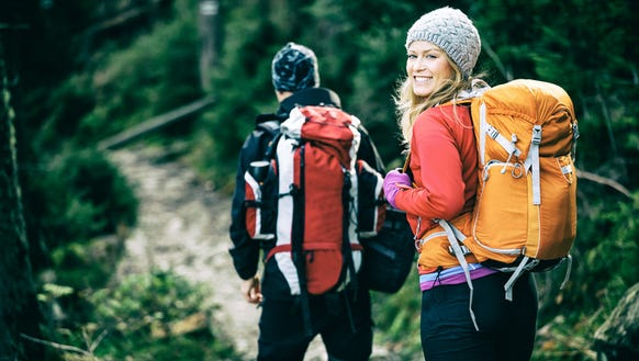 Man and woman hikers trekking in mountains. Young couple
